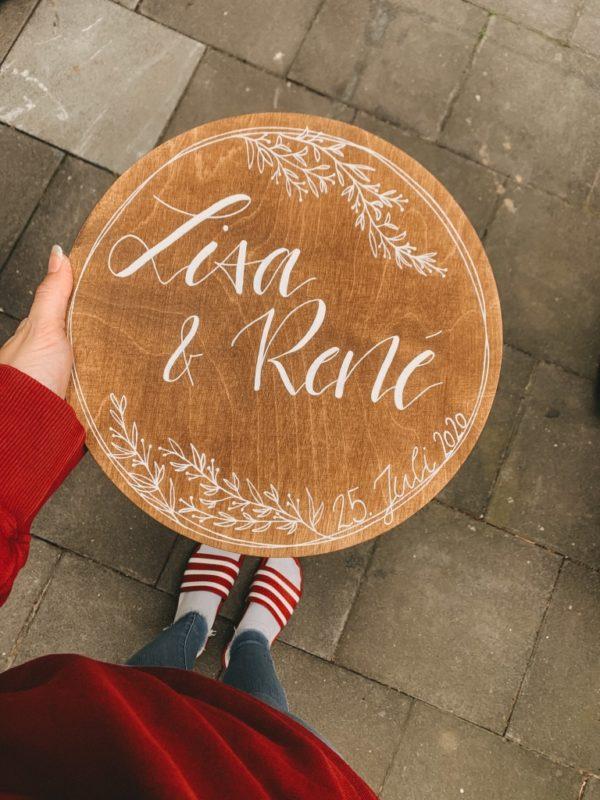 Personalisiertes Holzschild mit deinen Namen und einem floralem Rahmen als Begrüßung für deine Hochzeit